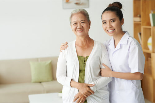 young nurse and senior woman looking at camera with smiles