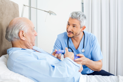 male caretaker explaining prescription to senior men in bedroom at nursing home