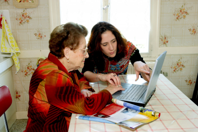 woman teaching senior woman how to do tele health home monitoring service